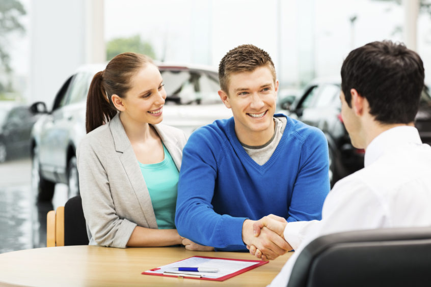 Happy young man shaking hands with salesperson at car showroom. Horizontal shot. Freelancers can deduct up to $18,000 as depreciation on cars and trucks driven for business purposes.